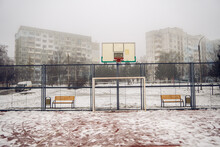 An Iron Basketball Court In The Snow, A Fence. Basketball Hoop Against The Background Of Residential Buildings In The Fog