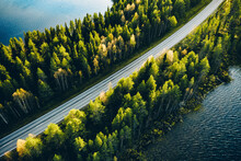 Aerial View Of Road Between Green Summer Forest And Blue Lake In Finland.