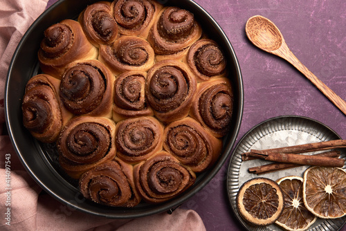 Fototapeta High angle shot of fresh cinnamon roll buns with a wooden spoon, cinnamon, and dried oranges obraz