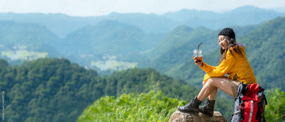 Fototapeta Asian women hiker or traveler with backpack adventure sitting and drinking ice coffee relax and rest on the mountain outdoor for destination leisure education nature on vacation