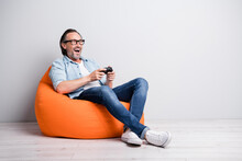 Full Length Photo Of Excited Man Happy Smile Play Video Game Sit Bean Bag Look Empty Space Isolated Over Grey Color Background