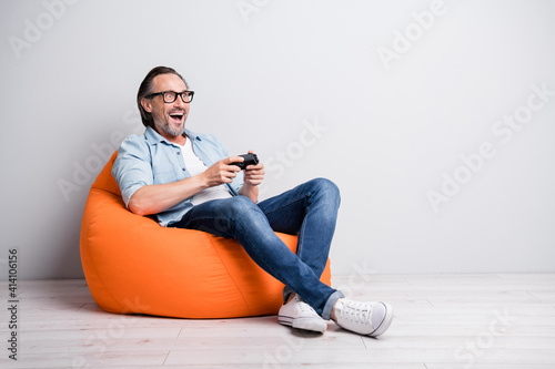 Fototapeta Full length photo of excited man happy smile play video game sit bean bag look empty space isolated over grey color background obraz