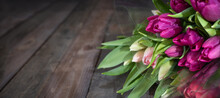 Bunch Purple Tulips On Dark Wooden Vintage Planks. Floristry Background With Short Depth Of Field And Space For Text.