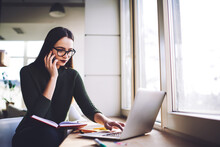 Businesswoman Talking On Smartphone While Browsing Laptop