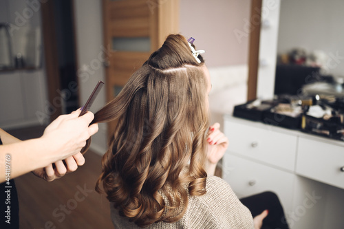 Hair stylist prepares beautiful young woman for event, makes curls hairstyle with a curling iron for client in beauty salon Fototapet