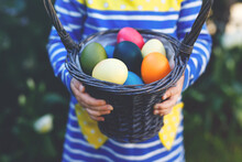 Close-up Of Of Hands Of Toddler Holding Basket With Colored Eggs. Child Having Fun With Traditional Easter Eggs Hunt, Outdoors. Celebration Of Christian Holiday