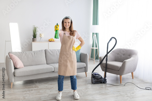 Obraz na plátně Full length portrait of young maid in apron and gloves pointing detergent spray