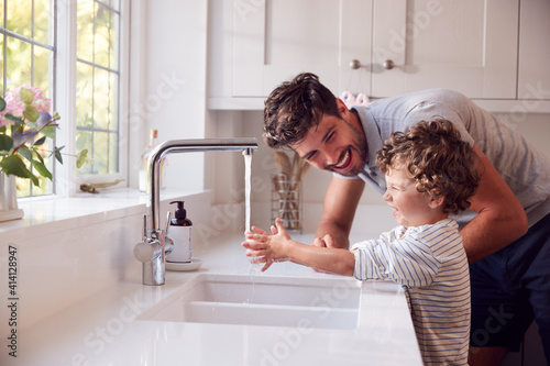 Fototapeta Father Helping Son To Wash Hands With Soap At Home To Stop Spread Of Infection In Health Pandemic obraz