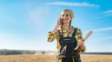 Farmer Using Her Phone On A Grain Field