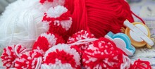 Close Up Red And White Yarn Strains Of Pompom Balls And Pompom Makers As Martenitsa - Bulgarian Folklore Tradition In March Baba Marta Day. Shallow Depth Of Focus. Colorful Yarn Texture Background.
