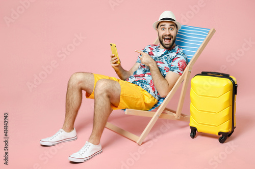 Fototapeta Full length excited young traveler tourist man in hat sit on deck chair pointing index finger on mobile cell phone isolated on pink background. Passenger travel on weekend. Air flight journey concept. obraz na płótnie