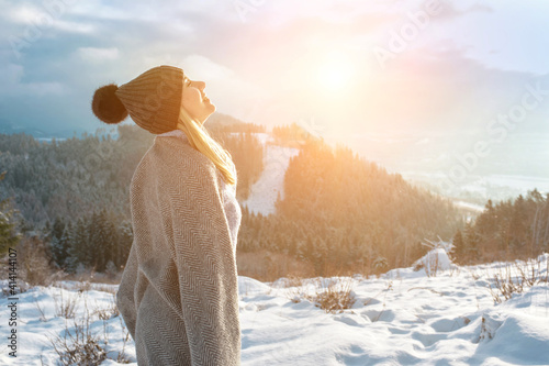 Fototapeta Happy woman traveler on the top of mountain and looking on beautiful winter snowy view