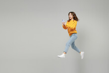 Full Length Of Young Fun Smiling Caucasian Student Woman 20s Wearing Knitted Yellow Sweater Jumping High Hold Mobile Cell Phone Chatting Typing Sms Isolated On Grey Color Background Studio Portrait..