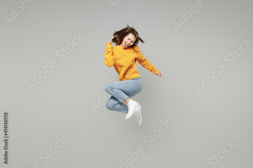 Vászonkép Full length of young excited overjoyed happy lucky positive attractive woman 20s wearing knitted yellow sweater do winner gesture clench fist jumping high isolated on grey background studio portrait