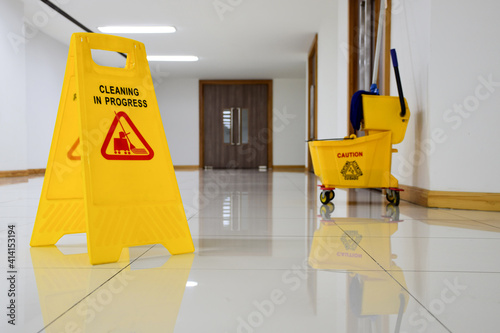 Close up yellow warning sign with message Cleaning in progress with cleaning trolley background