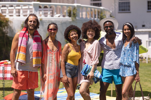 Portrait of diverse group of friends looking at camera and smiling at a pool party