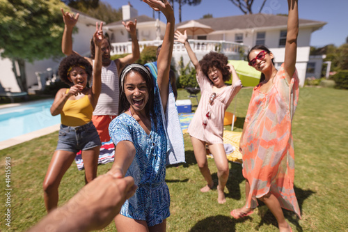 Diverse group of friends having fun and smiling at a pool party