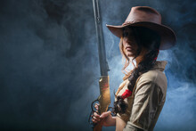 Portrait Of A Beautiful Brunette Cowgirl With A Rifle On A Background Of Smoke