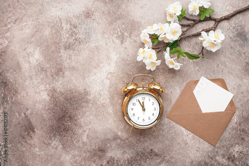 Fototapeta Spring time. Gold alarm clock, blank white card mockup in an envelope and flowering cherry branch artificial. Beige grunge background. Top view, flat lay. obraz