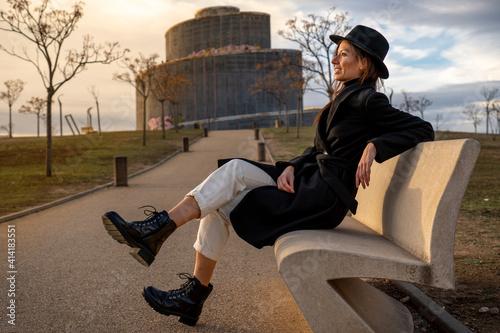 Obraz na plátně Chica con sombrero y abrigo negro posando en el parque en una tarde de invierno