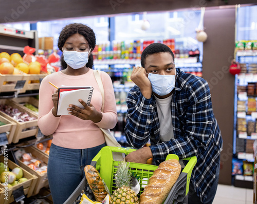Young woman in face mask checking grocery list at supermarket, her boyfriend sick and tired of shopping © Prostock-studio