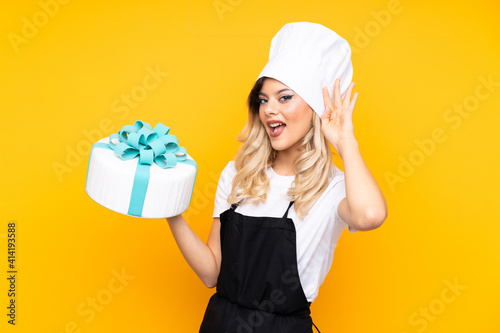 Canvas Print Teenager girl pastry holding a big cake isolated on yellow background listening