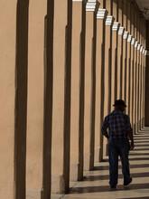 Cuba, Cienfuegos, Man Walking In Colonnade.