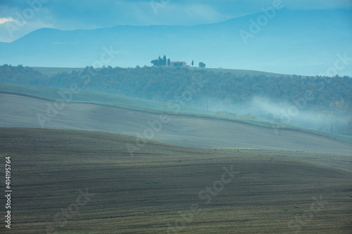 Fototapeta premium landscape with agricultural field, hills and fog