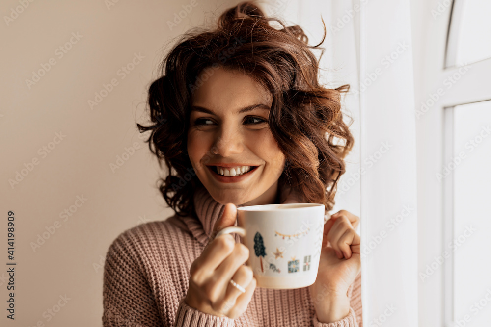 Fototapeta Charming adorable lady with curls holding a cup and looking aside near the window in sunny warm day