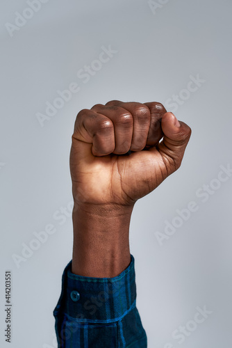 Close up shot of raised fist of african american guy in checkered shirt posing i Fototapet