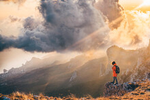 Man Hiker With Large Backpack Standing At The Cliff Against Large Distant Mountains Under Sky With Heavy White Clouds In Autumn Morning