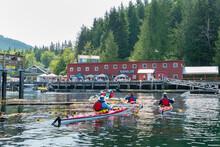 Canada, British Columbia. Sea Kayakers Paddle Into Telegraph Cove On Johnstone Strait, Vancouver Island.