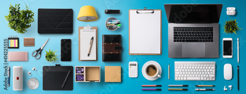 Obraz Flat lay top view office desk working space with laptop and supplies on blue background. - fototapety do salonu
