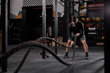 Athletic Man Doing Cross Fit Exercises With Rope At Gym, Concentrated And Focused On Training, Workout. People And Sport, Cross Fit Concept