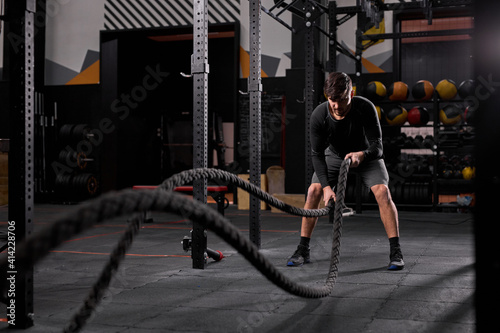 Slika na platnu Athletic man doing cross fit exercises with rope at gym, concentrated and focused on training, workout