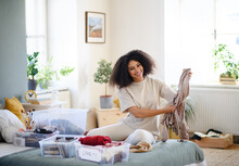 Young Woman Sorting Clothing Indoors At Home, Charity Donation Concept.