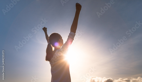 Fototapeta Feeling inspired. Young woman with fist up to sky feeling strong and motivated.  obraz