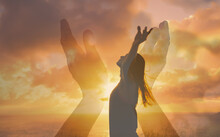 Silhouette Of A Woman With Arms Up In The Sunset Hands Reaching Out To Sky, Warm Rays Of Sunshine. Happiness And Worship Concept.
