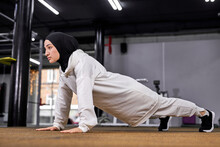 Sporty Muslim Woman Doing Push Ups, Fitness Woman Working Out Plank Exercise. Motivated Female In Hijab Enjoys Training On Floor At Gym