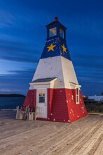 Canada, Nova Scotia, Cabot Trail. Cheticamp, Town Harbor. With Lighthouse Painted In Traditional Acadian Colors.