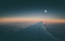 Wing Of An Airplane Flying In The Early Morning With The Moon Yet In The Sky