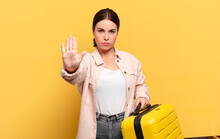 Young Pretty Woman Looking Serious, Stern, Displeased And Angry Showing Open Palm Making Stop Gesture