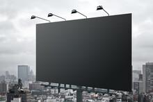 Huge Blank Black Outdoor Billboard With Lights On Top At City Background. Mockup
