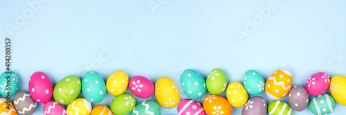 Obraz Colorful Easter Egg bottom border over a pastel blue paper banner background. Copy space. - fototapety do salonu