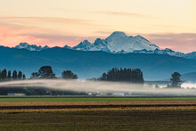 Ribbon Of Mist Across The Skagit Valley As Volcanic  Mount Baker Stands On The Horizon