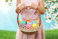 Little Girl With Basket Full Of Easter Eggs On Green Grass Outdoors, Closeup