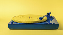 Blue And Yellow Vintage Vinyl Record Player On A Yellow Background.