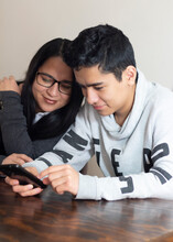 Young Mom With Latino Teenage Son Watching Cell Phone. Concept Children Teach Their Parents To Use Technology.
