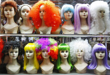 Lots Of Multicolored Female Wigs On Mannequin Heads In A Shop Window