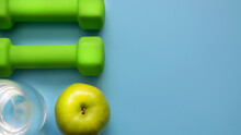 Dumbbells With An Apple On A Beige Background. Sports And A Healthy Lifestyle In The Modern World